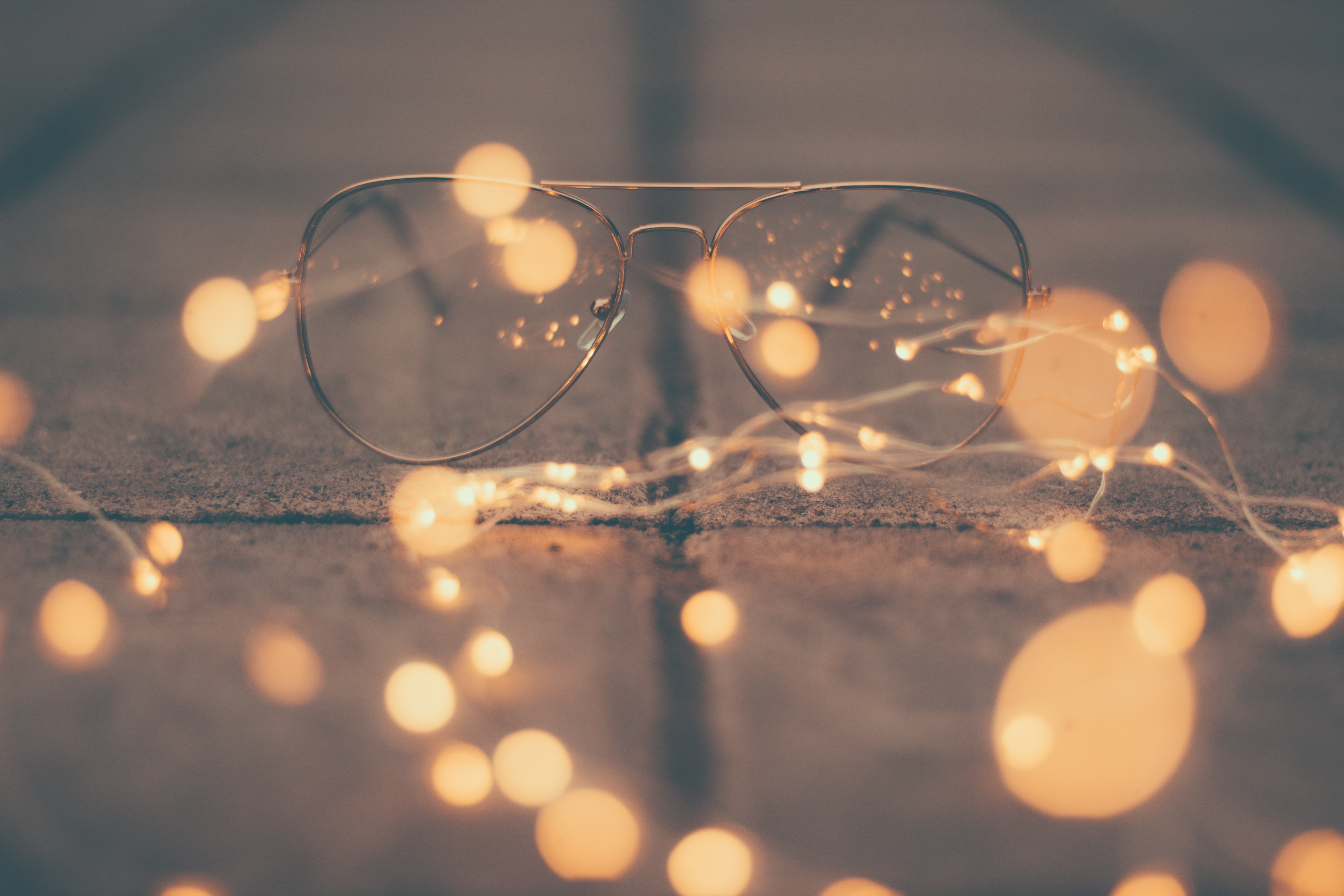 Aviator glasses on the ground in a shadowy light and surrounded by a string of lights.