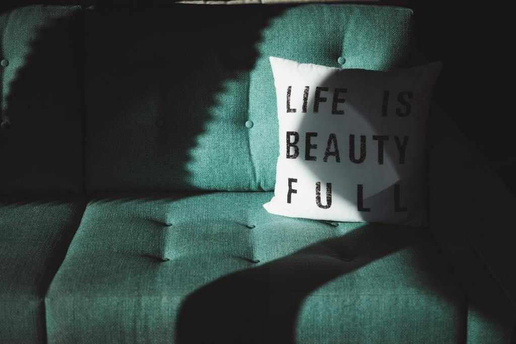 Green couch by a window in part sunlight and part shadow. White square pillow sitting on the couch with three lines in black block lettering: LIFE IS BEAUTY FULL.