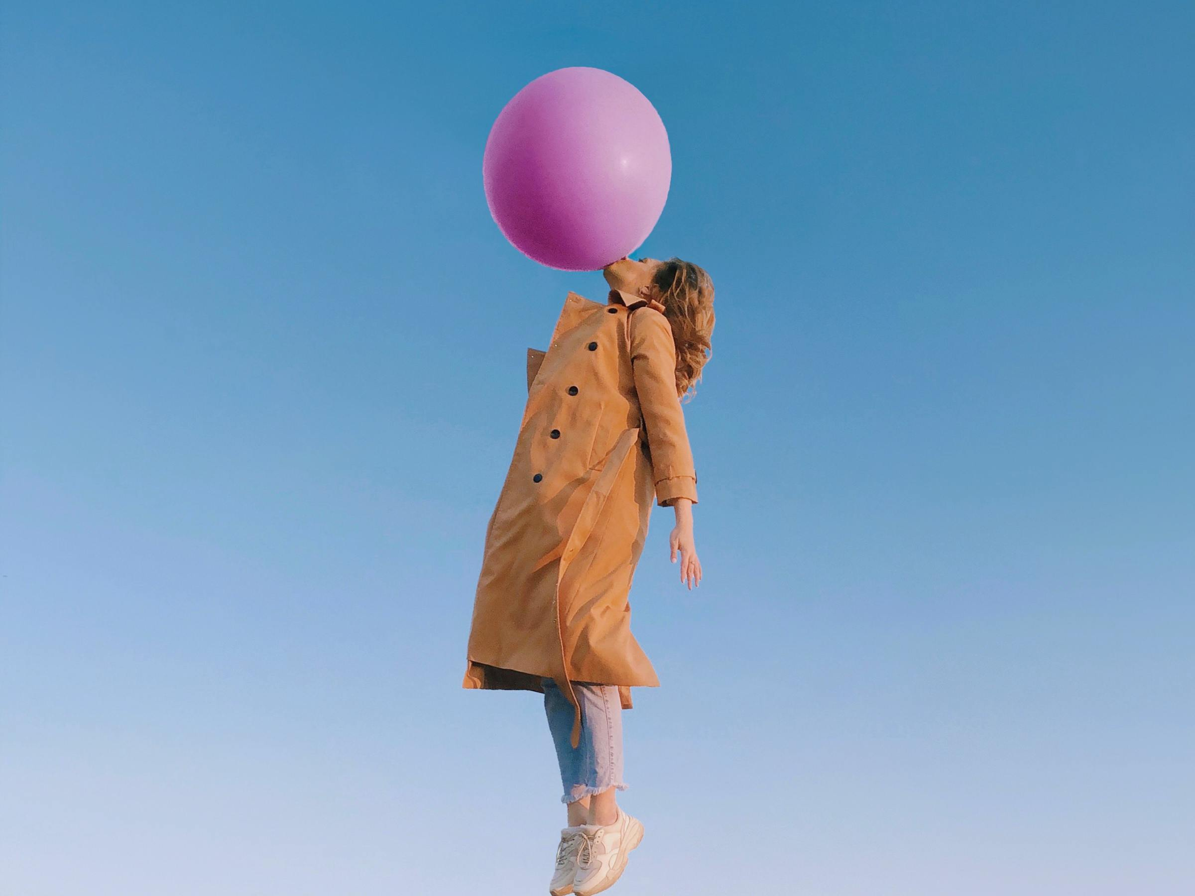 Woman in overcoat, jeans and tennis flying straight up with her mouth on a big pink balloon. She is ascending like Mary Poppins.