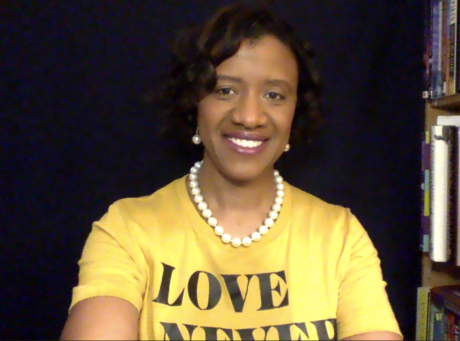 Dr. Shaunta in gold t-shirt with message Love Never Fails. Seated with pearls on in front of navy blue background and next to bookcase